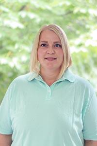 Profilbild von blonder Frau in türkisfarbenem Poloshirt