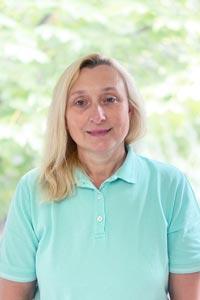 blonde Frau in türkisfarbenem Poloshirt